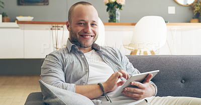 Buy stock photo Cropped portrait of a handsome young man smiling while using a digital tablet in his living room at home