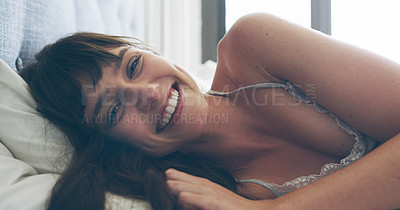 Buy stock photo Cropped portrait of an attractive young woman smiling while lying in her bed at home