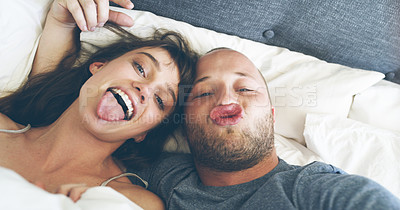 Buy stock photo High angle portrait of an affectionate young couple making silly faces while taking a selfie in their bed at home