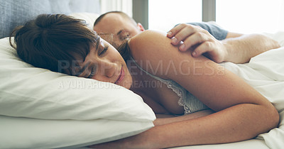 Buy stock photo Cropped shot of an affectionate young couple sleeping together in their bed at home