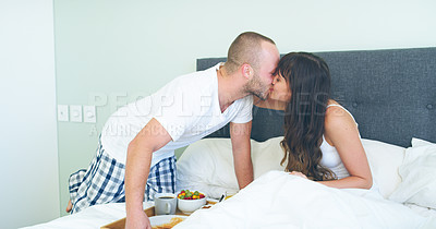 Buy stock photo Cropped shot of an affectionate young man kissing his wife after making her breakfast in bed at home
