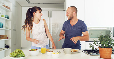 Buy stock photo Cropped shot of an affectionate young couple laughing together while having breakfast in their kitchen at home