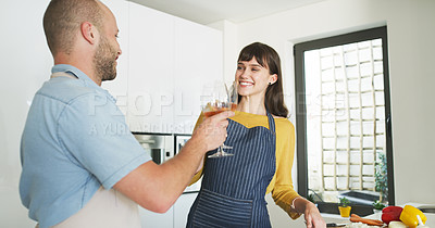 Buy stock photo Cropped shot of an affectionate young couple making a toast with wine glasses while cooking in their kitchen at home