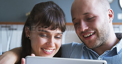 Buy stock photo Cropped shot of an affectionate young couple using a digital tablet together in their living room at home