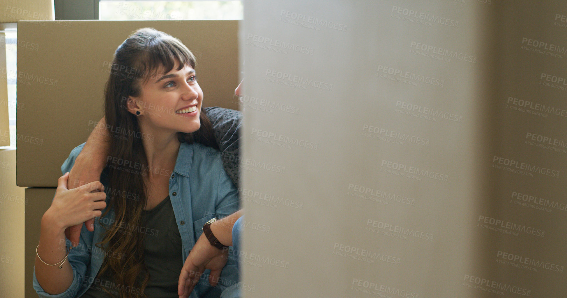 Buy stock photo Cropped shot of an affectionate young woman smiling at her husband while sitting in their new home on moving day