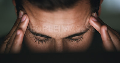 Buy stock photo Closeup shot of a young businessman suffering with a headache while working in an office at night