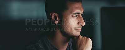 Buy stock photo Shot of a young businessman looking thoughtful while working in an office at night