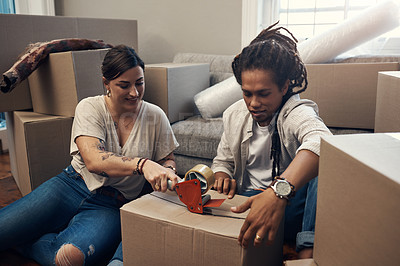 Buy stock photo Cropped shot of a young couple taping up boxes at home