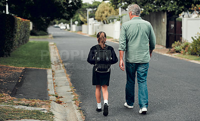 Buy stock photo Full length shot of a young school girl walking with her grandfather to school in the streets in their neighborhood