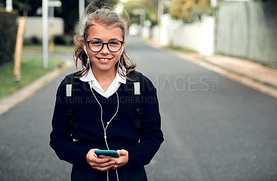 Buy stock photo Portrait of an adorable young schoolgirl listening to music and using her cellphone while walking to school