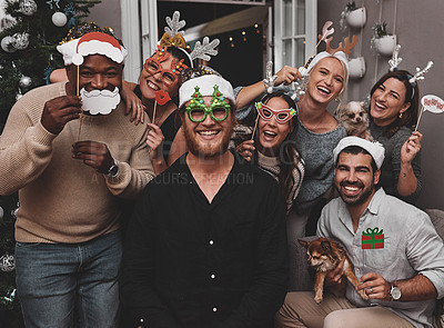 Buy stock photo Portrait of a cheerful group of friends wearing festive hats while posing for a photo together at home during christmas time