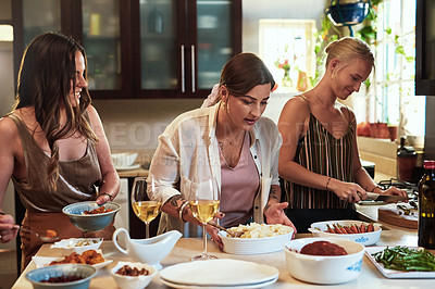 Buy stock photo Cropped shot of a group of cheerful young friends preparing food in the kitchen together at home during the day