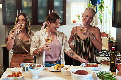 Buy stock photo Cropped shot of a group of cheerful young friends preparing food in the kitchen together while drinking wine at home during the day