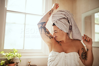 Buy stock photo Shot of an attractive young woman smelling her armpits during her morning beauty routine
