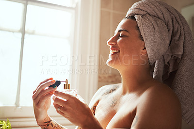 Buy stock photo Shot of a young woman spraying perfume during her morning beauty routine