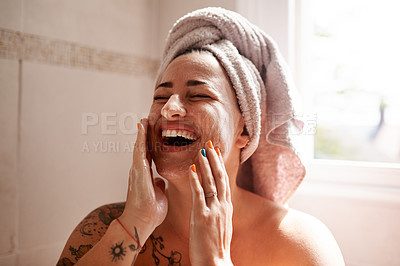 Buy stock photo Shot of a young woman giving herself a facial at home