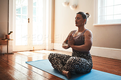 Buy stock photo Shot of a young woman meditating on a yoga mat at home
