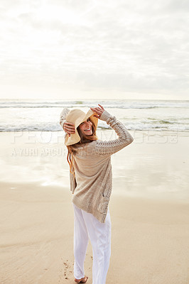 Buy stock photo Portrait of a young woman standing with her arms outstretched at the beach