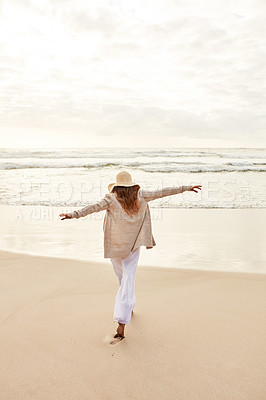 Buy stock photo Rearview shot of a young woman standing with her arms outstretched at the beach