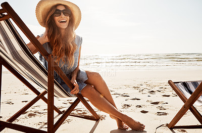 Buy stock photo Shot of a young woman relaxing on a lounger at the beach