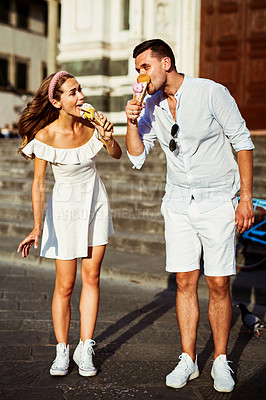 Buy stock photo Shot of a happy young couple eating ice cream while touring the city of Florence