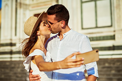 Buy stock photo Shot of a happy young couple taking selfies while touring the city of Florence
