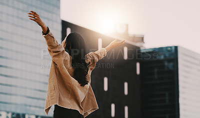 Buy stock photo Shot of a young woman standing with her arms outstretched in the city