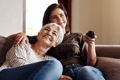 Buy stock photo Shot of a young woman watching tv with her elderly mother at home
