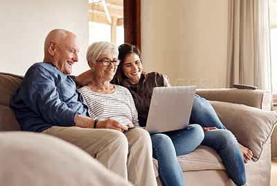 Buy stock photo Shot of a young woman using a laptop and credit card with her elderly parents on the sofa at home