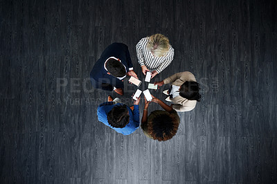 Buy stock photo High angle shot of a group of businesspeople using their phones in synchronicity in a modern office