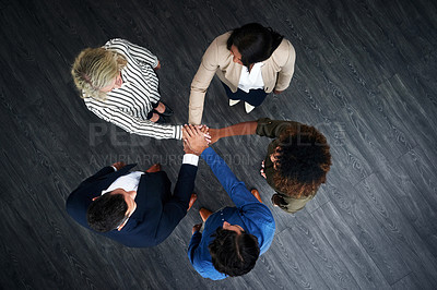Buy stock photo High angle shot of a group of businesspeople joining hands in solidarity in a modern office