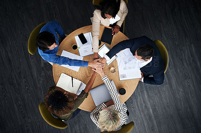 Buy stock photo High angle shot of a group of businesspeople joining hands during a meeting in a modern office