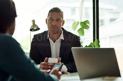 Buy stock photo Shot of two businessmen using their cellphones while having a discussion in an office