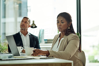 Buy stock photo Shot of a mature businesswoman working on a laptop alongside a colleague in an office