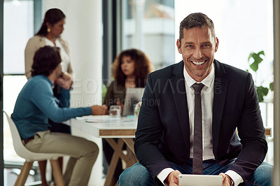 Buy stock photo Portrait of a mature businessman using a digital tablet in an office with his colleagues in the background
