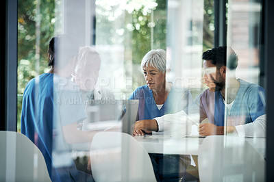 Buy stock photo Shot of a group of medical practitioners having a discussion in a hospital boardroom