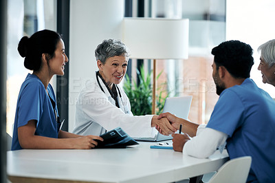Buy stock photo Shot of medical practitioners shaking hands during a meeting in a hospital boardroom
