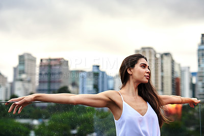 Buy stock photo Cropped shot of an attractive young woman standing on a balcony with her arms outstretched during the day