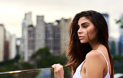 Buy stock photo Cropped shot of an attractive young woman standing on a balcony outdoors during the day