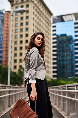 Buy stock photo Cropped portrait of an attractive young woman looking back while walking in the city during the day