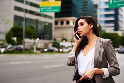 Buy stock photo Cropped shot of an attractive young businesswoman taking a phonecall while commuting in the city during the day