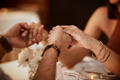Buy stock photo Cropped shot of an unrecognizable couple holding hands during their date at a restaurant