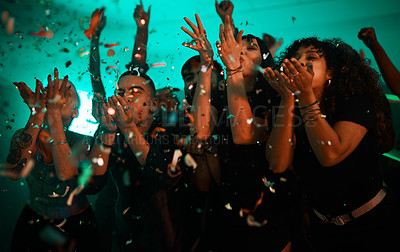 Buy stock photo Cropped shot of a diverse group of young friends blowing confetti while partying in a club at night