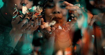Buy stock photo Closeup shot of two young girlfriends blowing confetti while partying in a nightclub