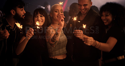 Buy stock photo Cropped shot of a diverse group of young friends holding up sparklers while partying in a nightclub