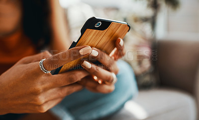 Buy stock photo Cropped shot of a woman using a smartphone while relaxing on the sofa at home