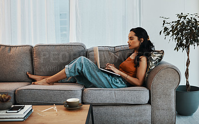 Buy stock photo Shot of a young woman using a laptop on the sofa at home