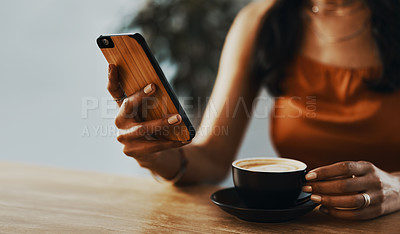 Buy stock photo Cropped shot of a woman using a smartphone and having coffee at home