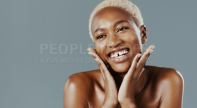 Buy stock photo Cropped shot of an attractive young woman standing with her hands on her face and smiling against a gray background
