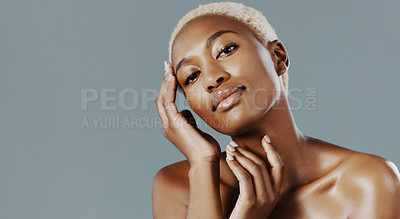 Buy stock photo Cropped shot of an attractive young woman standing alone with her hands on her face against a gray studio background